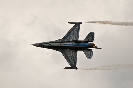military aircraft: f-16 fighter jet doing aerobatics at an airshow Editorial
