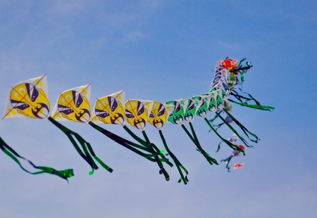 a string of colorful chinese kites depicting chinese traditional masks are floating before blue sky photo