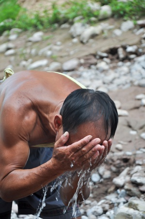 a chinese farmer is washing his face in a river photo