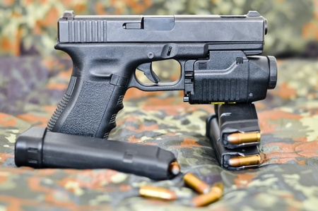 9mm military sidearm with a tactical laser/light-module on camouflage Stock Photo - 10262574