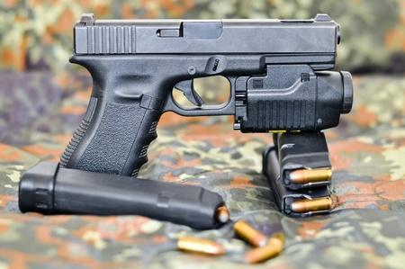 9mm pistool met een militaire tactische laser  licht-module op de camouflage Stockfoto