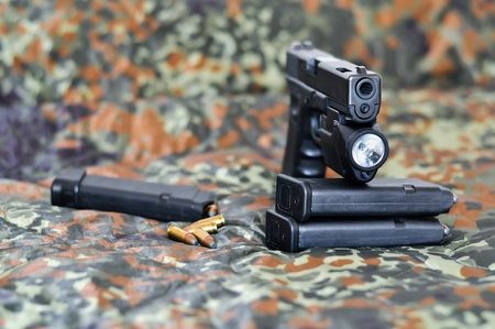 9mm military sidearm with a tactical laserlight-module on camouflage photo