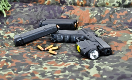 sidearm: military sidearm with a tactical laserlight-module on camouflage Stock Photo
