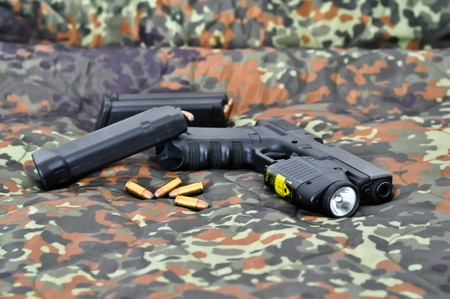 automatic pistol: 9mm military sidearm with a tactical laserlight-module on camouflage