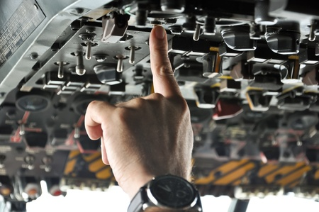 finger of a pilot pushing buttons in an airplane cockpit photo