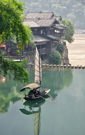lone chinese fishing boat on an emerald pond