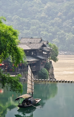 fishing village: lone chinese fishing boat on an emerald pond
