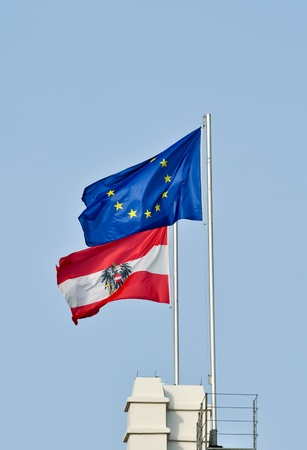 flags of austria and the european union flying together against a blue sky photo