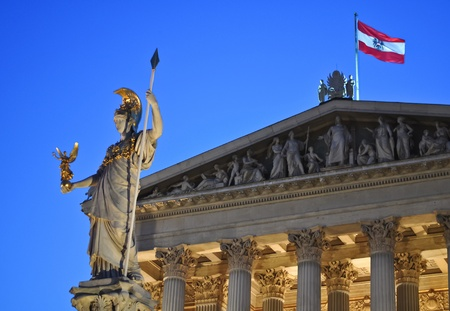 statue of pallas athene in front of the austrian parliament in vienna at night photo