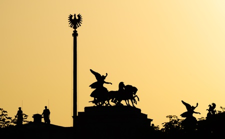 silhouette of statues atop the austrian parliament in vienna against the sunset photo