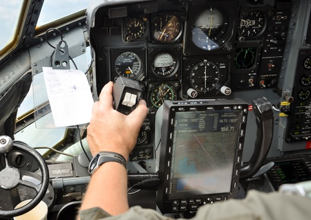 closeup of a pilots hand steering a military cargo plane