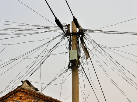 transformator: entangled power lines going out from a landline Stock Photo