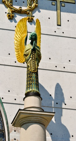 statue of a golden art nouveau angel praying on vienna photo