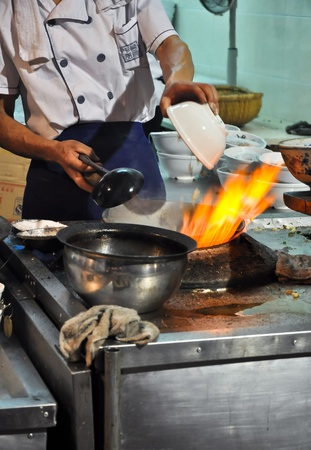 stir fry: asian cook cooking with a wok on a gas flame