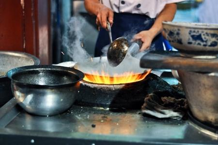 Aziatische kok koken met een wok op een gasvlam Redactioneel