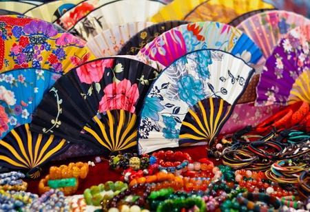 een verzameling van kleurrijke Chinese waaiers en een aantal armbanden
