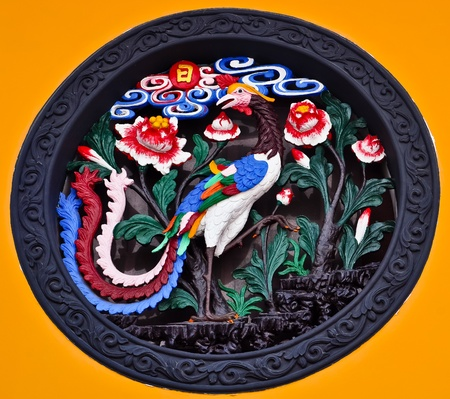 chinese ornament depicting a colorful peacock and flowers photo
