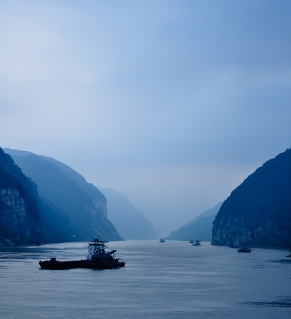freighter: an evening scene on the yangze river in blue light with cargo ships