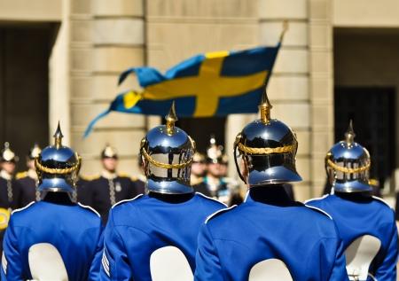 bandera de suecia: soldados suecos con cascos brillantes en frente del palacio Real de Estocolmo