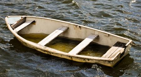lekkende reddingsboot gevuld met water Stockfoto