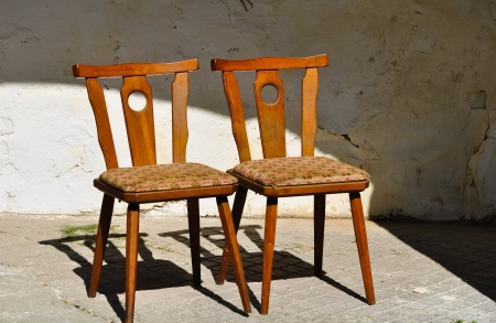 two old wooden chairs are standing close on an old porch Stock Photo - 13871903