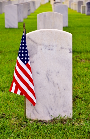 tombstone on a national cemetery with the american flag photo