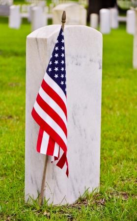 grafstenen op een nationale begraafplaats met de Amerikaanse vlag