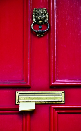 red wooden door with brass knockers and letters sticking in the letterbox photo