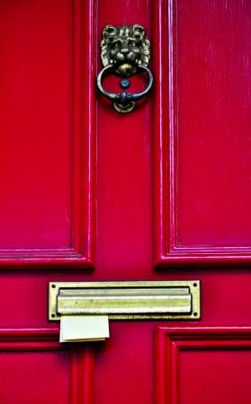 rode houten deur met koperen kloppers en letters plakken in de brievenbus