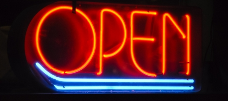 stating: neon sign in a dark window stating open