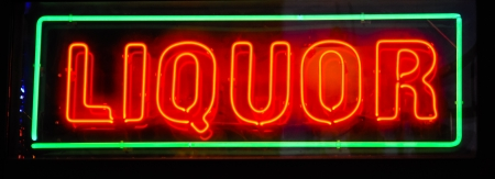 neon sign in a dark window advertising liquor photo