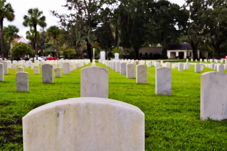 tombstones on a national cemetery with the american flag photo