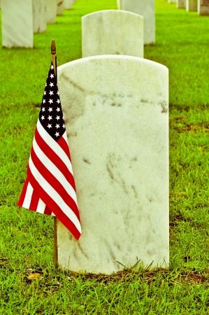 sacrificio: foto de época de lápidas en un cementerio nacional con la bandera americana