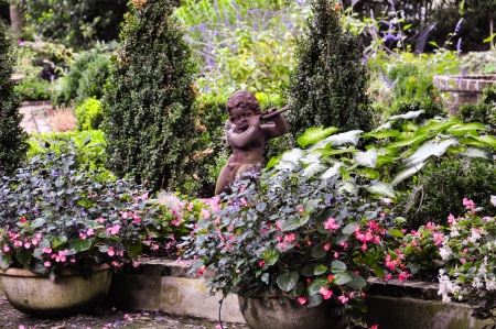 faun: little ceramic staute of a faun playing the flute  in between colorful flowers