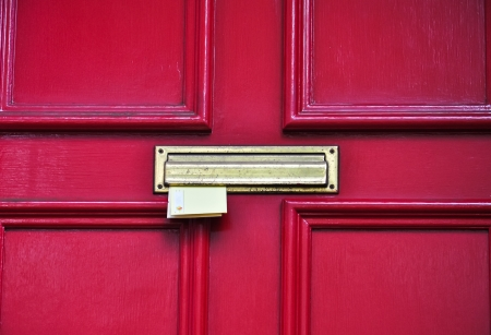 letter sticking out of red door photo