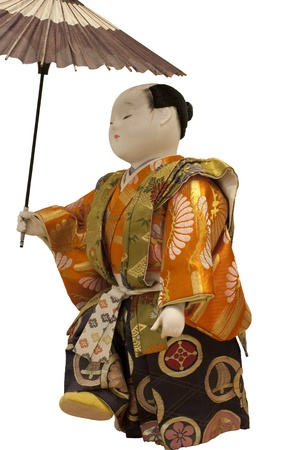 a doll of ancient japanese man holding an umbrella