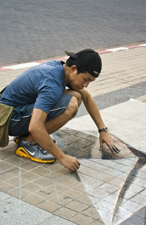 CHIANG MAI, THAILAND - MARCH 23: A young artist with his leather bag during drawing and painting his artwork on street in  Chiang Mai Fest and Art on the Street 2012,Chiang Mai, Thailand on 23 March,2012.