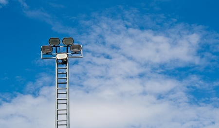 tower of spot-light or flood light against bright blue sky  photo