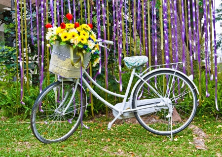 artificial flowers: decorative old white painted  bicycle with basket of colorful flower Stock Photo