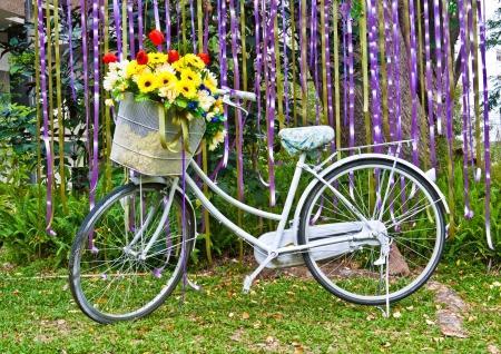 decorated bike: decorativo vecchia bicicletta dipinta di bianco con cesto di fiori colorati