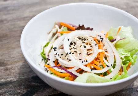 a bowl of fresh vegetable salad,side dish, onion,cabbage,carot,sesame