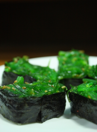 japanese sushi with rice and chuka wakami  green seaweed  on top photo