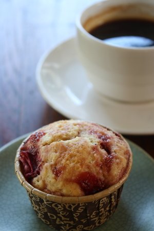 muffin mix with berry with cup of hot black coffee