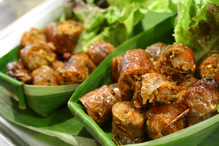 chopped Thai herbal sausage in banana leaf cup with lettuce Stock Photo