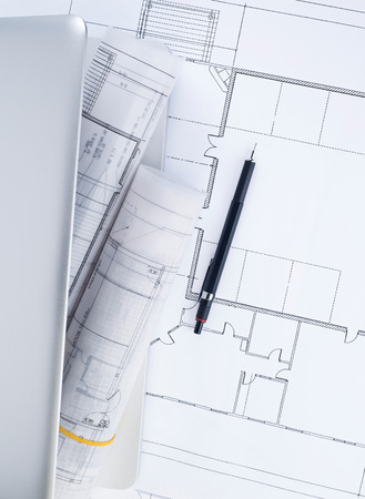 housing problems: Blueprints and laptop Stock Photo