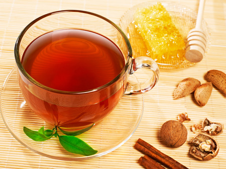 Cup of tea with cinnamon,honey and nuts, isolated on white