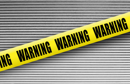 Warning tape on metal background photo
