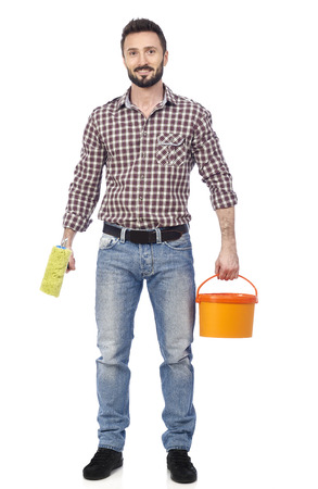 redecoration: Cheerful man holding a paint roller and a paint bucket, looking at camera Stock Photo