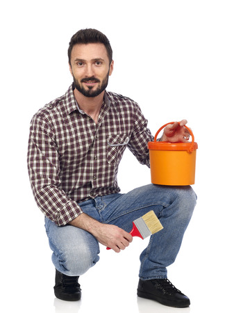 redecoration: Cheerful man holding a paint brush and a paint bucket, looking at camera Stock Photo