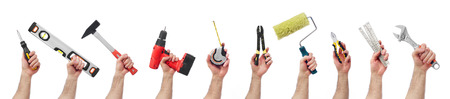 building contractor: Hands raised holding different tools Stock Photo